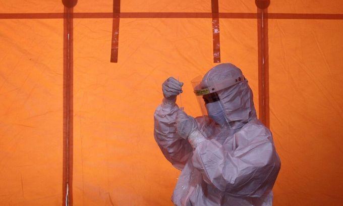 Nhân viên y tế cầm một mẫu sinh phẩm xét nghiệm Covid-19 tại Yogyakarta, Indonesia hôm 3/1. Ảnh: Reuters.