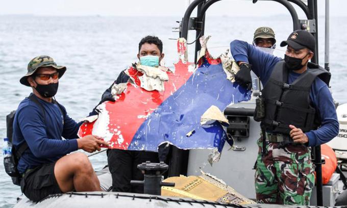 Hải quân Indonesia hôm 10/1 cầm một mảnh vỡ được tin là thuộc về máy bay gặp nạn của Sriwijaya Air trong lúc tìm kiếm trên vùng biển ngoài khơi Jakarta. Ảnh: Reuters.