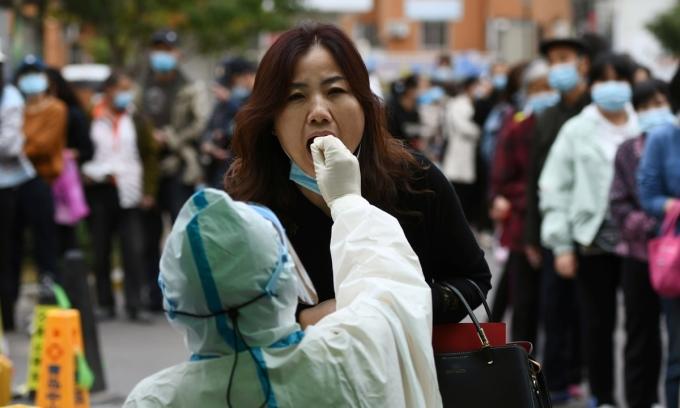 Một phụ nữ làm xét nghiệm nCoV tại Thanh Đảo, Trung Quốc hôm 13/10/2020. Ảnh: Reuters.