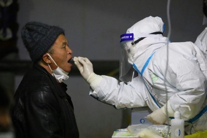 Cán bộ y tế lấy mẫu xét nghiệm Covid-19 của người dân ở Thạch Gia Trang. Ảnh: AFP
