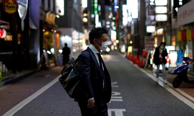 Người đàn ông đeo khẩu trang trên đường phố thủ đô Tokyo, Nhật Bản hồi tháng trước. Ảnh:Reuters.