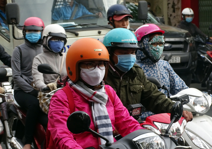 Người dân TP HCM ra đường mang áo khoác, khăn quàng cổ, sáng 13/1. Ảnh: Hà An.