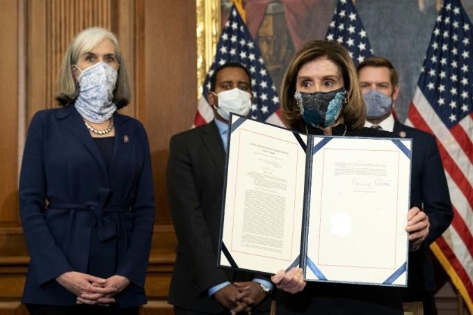 Chủ tịch Hạ viện Nancy Pelosi ký điều khoản xem xét bãi nhiệm Trump ngày 13/1. Ảnh: AFP.
