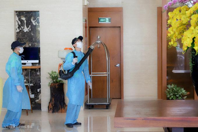 Nhân viên y tế phun khử khuẩn một khách sạn cách ly người nước ngoài nhập cảnh. Ảnh: Nguyễn Đông.