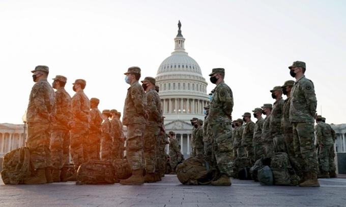 Một nhóm binh sĩ Vệ binh Quốc gia tập hợp bên ngoài tòa nhà quốc hội ở Washington DC, Mỹ, trước khi Hạ viện họp bỏ phiếu xem xét bãi nhiệm Tổng thống Donald Trump. Ảnh: Reuters.