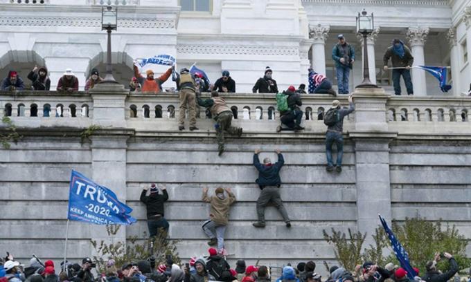 Những người ủng hộ Tổng thống Trump trèo lên bức tường phía tây tòa nhà quốc hội ở Washington DC ngày 6/1. Ảnh: AP.