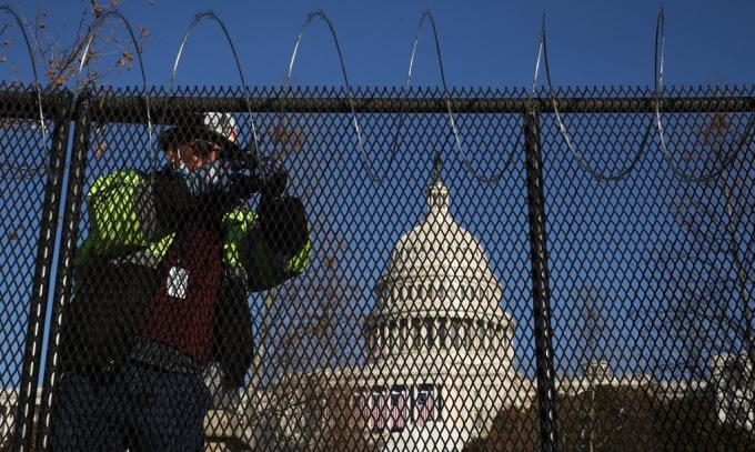 Công nhân lắp hàng rào và lưới thép gai quanh Đồi Capitol hôm 14/1. Ảnh: AFP.