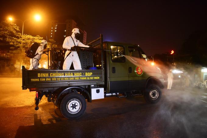 Hơn 100 chiến sĩ Binh chủng Hóa học (Bộ Quốc phòng) phun khử khuẩn toàn bộ Bệnh viện Bạch Mai, tối 28/3. Ảnh: Giang Huy.