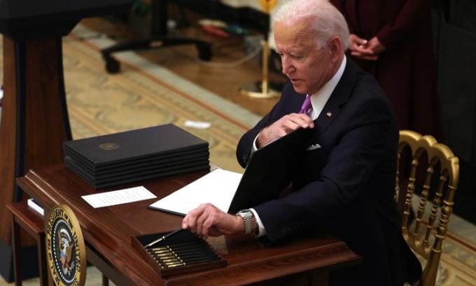 Tổng thống Mỹ Joe Biden ký các sắc lệnh ngăn Covid-19 ở Nhà Trắng hôm 21/1. Ảnh: AFP.