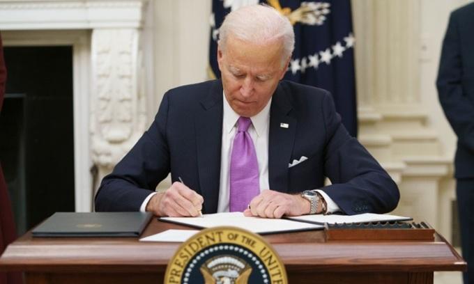 Tổng thống Mỹ Joe Biden ký sắc lệnh Covid-19 tại Nhà Trắng hôm 21/1. Ảnh: AFP.