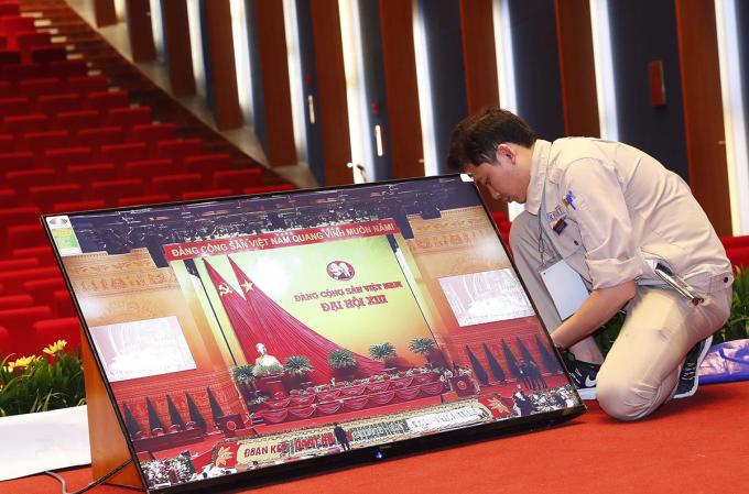Nhân viên kỹ thuật lắp đặt những màn hình lớn phục vụ Đại hội. Ảnh: TTXVN