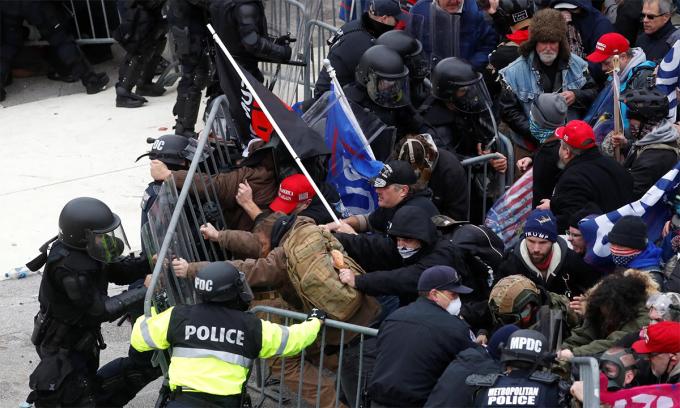 Cảnh sát quốc hội Mỹ cố ngăn người biểu tình quá kích phá hàng rào an ninh, ngày 6/1. Ảnh: Reuters.