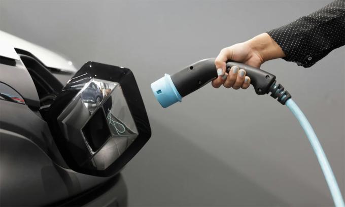Một phụ nữ cầm cáp sạc ôtô điện. Hết điện giữa hành trình là nỗi lo chủ yếu của các tài xế. Ảnh: Reuters