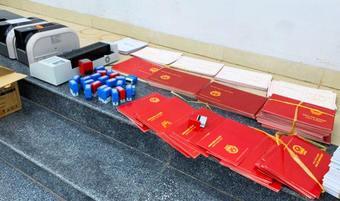 Phôi bằng, con dấu và máy móc các nghi phạm dùng để làm giấy tờ giả. Ảnh: Quang Bình.