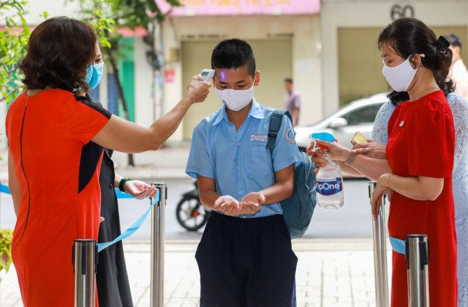 Học sinh Tiểu học Đinh Tiên Hoàng (quận 1, TP HCM) đến trường học vào tháng 5/2020 sau hơn 3 tháng nghỉ vì Covid-19. Các em được do thân nhiệt, rửa tay, đeo khẩu trang trước khi vào lớp. Ảnh: Quỳnh Trần