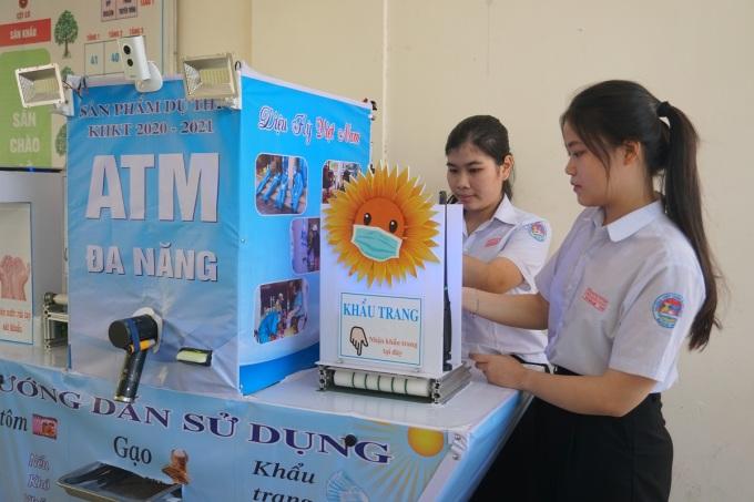 Thư và Thủy bên máy ATM phát gạo, khẩu trang, mỳ tôm và rửa tay sát khuẩn. Ảnh: Phạm Linh.