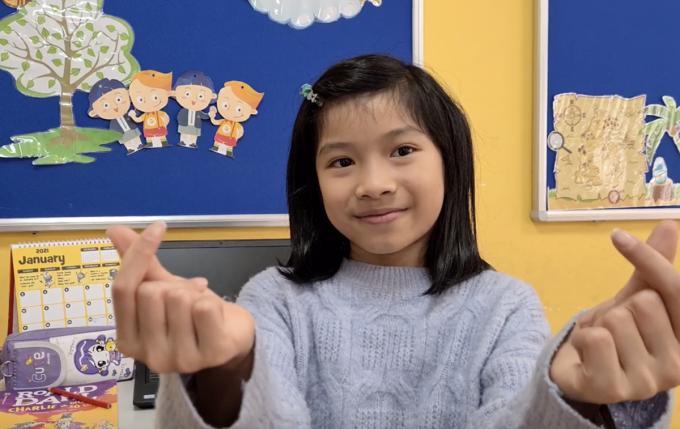 Đinh Thiện Giang, thành viên Edison Kids Radio, thả tim chúc các bạn trường Tiểu học Xuân Phương luôn vui vẻ, khoẻ mạnh. Ảnh: Nhà trường cung cấp.