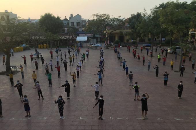 Học sinh trong khu cách ly trường THCS Sao Đỏ tập thể dục nâng cao sức khoẻ trong khu cách ly. Các em vẫn tuân thủ quy định giãn cách, đeo khẩu trang. Ảnh: Nhân vật cung cấp.