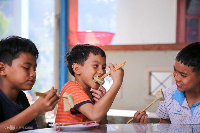 Học sinh trường THCS Trà Leng thích thú thưởng thức bánh chưng do mình tự tay gói được. Ảnh: Nguyễn Đông.