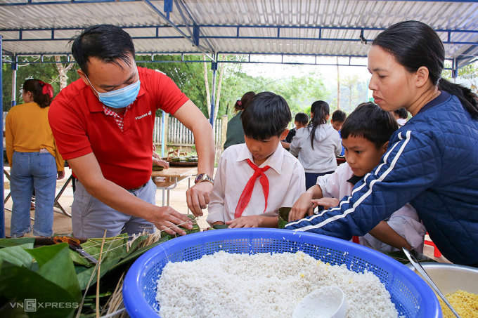 Ông Nguyễn Duy Hiền, đại diện Vietlott cùng gói bánh chưng với học sinh Trà Leng. Ảnh: Nguyễn Đông.