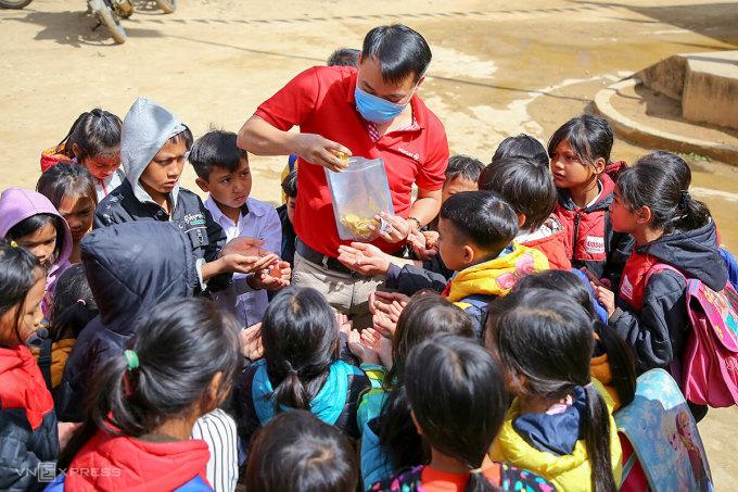 Học sinh Phước Thành thích thú với những món ăn ngày Tết. Mỗi em còn được nhận một phần quà trị giá 50.000 đồng để mang về nhà. Ảnh: Nguyễn Đông.