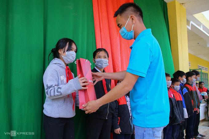Ông Nguyễn Đắc Thành, đại diện Quỹ Hy Vong tặng quà cho học sinh xã Phước Kim. Ảnh: Nguyễn Đông.