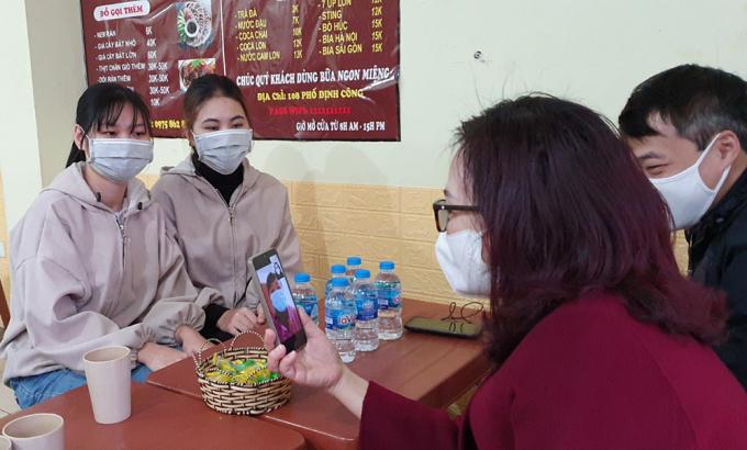 Cô Nhung trò chuyện với phụ huynh qua điện thoại trong lúc đến gặp gỡ, trao quà cho sinh viên ở khu Định Công, trưa 9/1. Ảnh: Ngọc Anh.