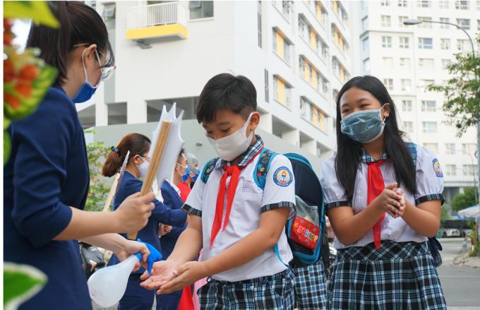 Học sinh trường Tiểu học Lê Đức Thọ, quận Gò Vấp được giáo viên đón trước cổng, giúp rửa tay, đo thân nhiệt trước khi vào lớp hồi tháng 5/2020. Ảnh: Mạnh Tùng.