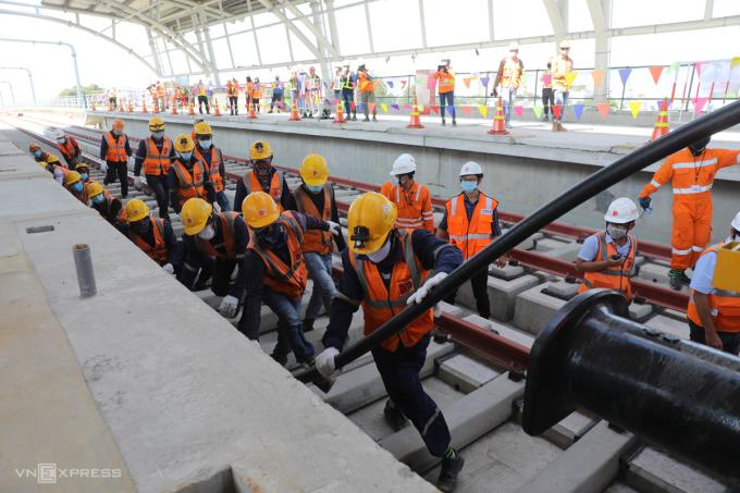 Công nhân kéo cáp thi công hệ thống điện tuyến Metro Số 1 sáng 19/2 tại đoạn đi qua TP Thủ Đức. Ảnh: Quỳnh Trần.