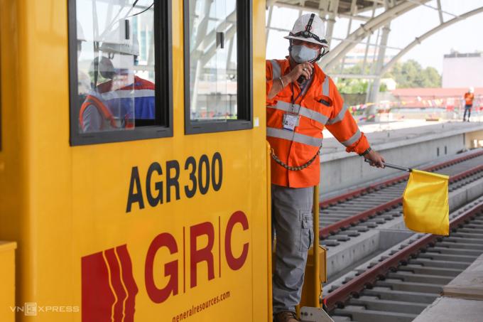 Kỹ sư thuộc nhà thầu Hitachi trên máy kéo cáp ra hiệu cho việc thi công hệ thống điện trên đoạn đường ray đi qua TP Thủ Đức, sáng 19/2. Ảnh: Quỳnh Trần.