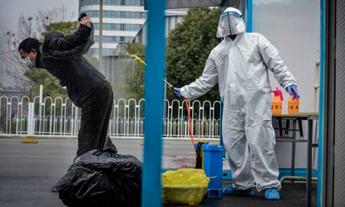 Người đàn ông được nhân viên y tế phun khử trùng tại bệnh viện ở Vũ Hán tháng 2/2020. Ảnh: AFP.