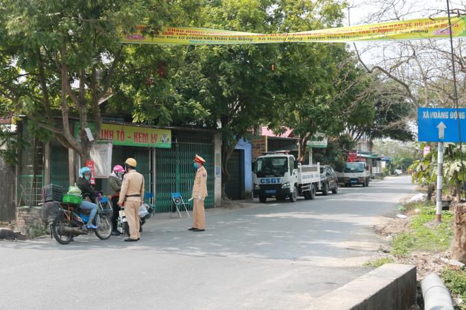 Lực lượng công an chốt chặn từ xa, ngăn không cho người và phương tiện ra vào xã Hoàng Động đang bị giãn cách xã hội và 1 thôn của xã này- Lôi Động bị phong tỏa, sau khi ghi nhận 2 chị em mắc nCoV. Ảnh: Giang Chinh