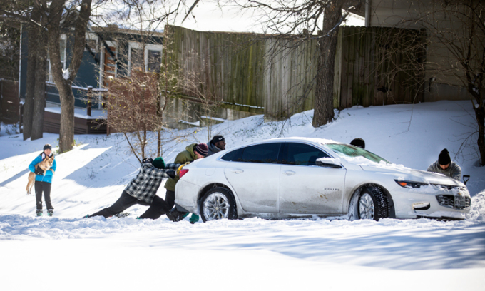 Người dân đẩy một chiếc xe bị mắc kẹt trong tuyết ở thành phố Austin, bang Texas, Mỹ tuần trước. Ảnh: AFP.
