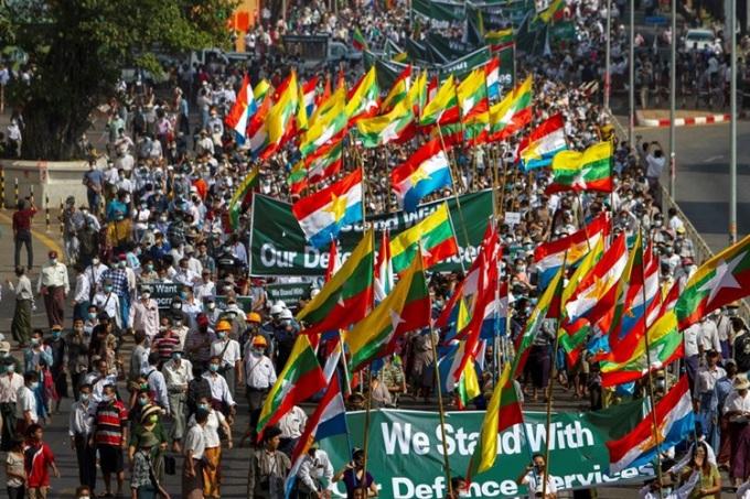 Nhóm ủng hộ quân đội Myanmar mang theo cờ và biểu ngữ tuần hành ở Yangon hôm nay. Ảnh: Reuters.
