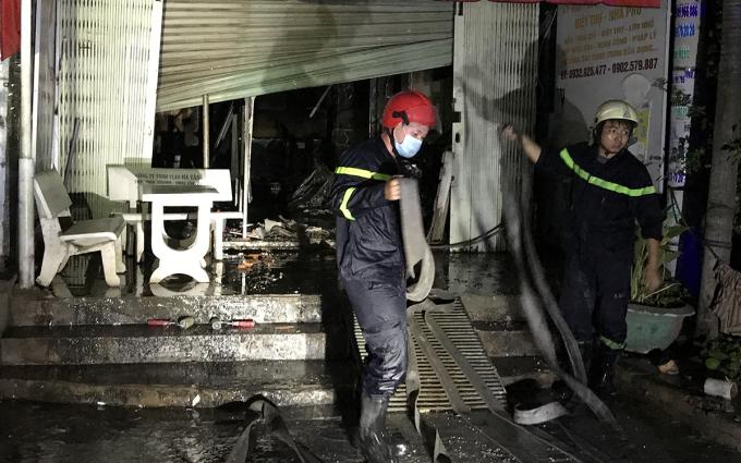 Cảnh sát phá cửa cuốn, kéo vòi rồng dập lửa. Ảnh: Đình Văn.
