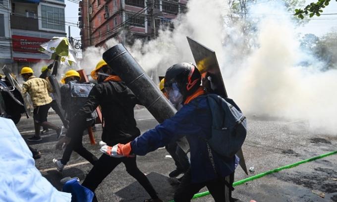 Người biểu tình Myanmar cầm khiên tự chế tháo chạy khi né đạn hơi cay từ lực lượng an ninh ở Yangon hôm 1/3. Ảnh: AFP.