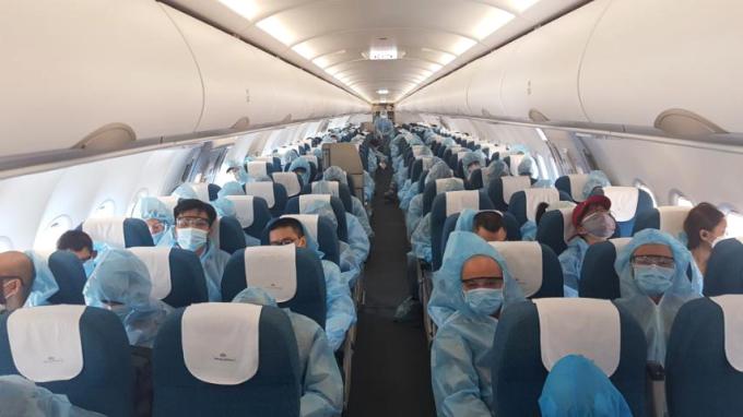 Hành khách người Việt mặc đồ bảo hộ trên máy bay. Ảnh: VNA.