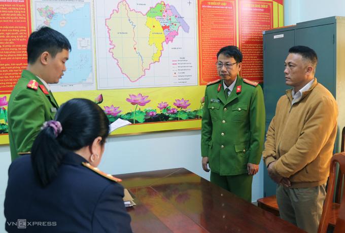 Ông Bình (phải) nghe đọc quyết định khởi tố. Ảnh: Quang Văn