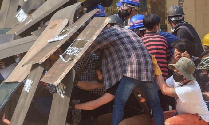 Người biểu tình núp sau những tấm khiên tự chế khi đối mặt lực lượng an ninh ở Bagan hôm nay. Ảnh: AFP.