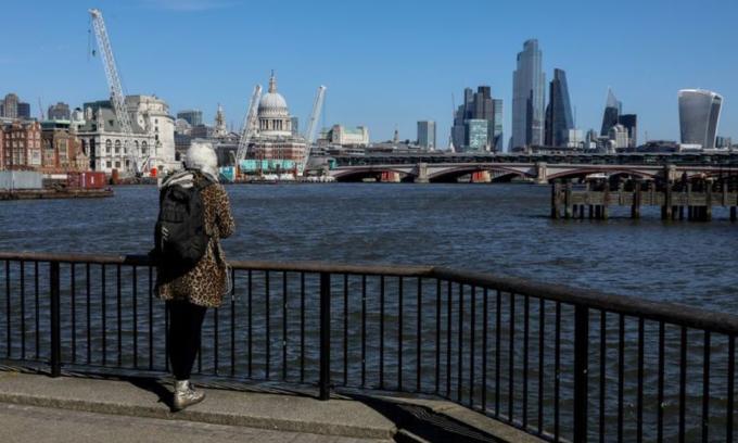 Một phụ nữ nhìn ra sông Thames ở thủ đô London, Anh, hồi tháng 3/2020. Ảnh: Reuters.