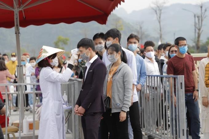 Tình nguyện viên đo thân nhiệt cho du khách tại cổng Tam Quan ngày 14/3. Ảnh: Việt Hà.