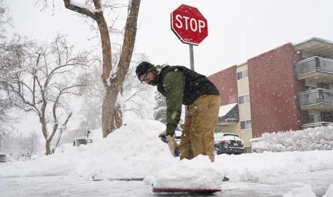 Một người dân ở Denver dọn tuyết trên đường hôm 14/2. Ảnh: AP