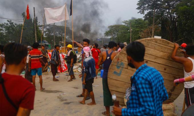 Khói bốc lên từ các nhà máy bị đốt ở khu công nghiệp Hlaingthaya, Yangon hôm 14/3. Ảnh: AFP.