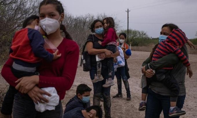 Người di cư chờ được đưa đi sau khi vượt biên từ Mexico đến Texas, Mỹ hôm 14/3. Ảnh: Reuters.
