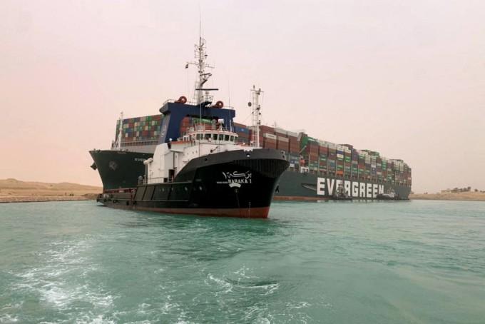 Tàu cứu hộ hoạt động quanh tàu Evergreen mắc kẹt ở kênh đào Suez hôm 24/3. Ảnh: AFP