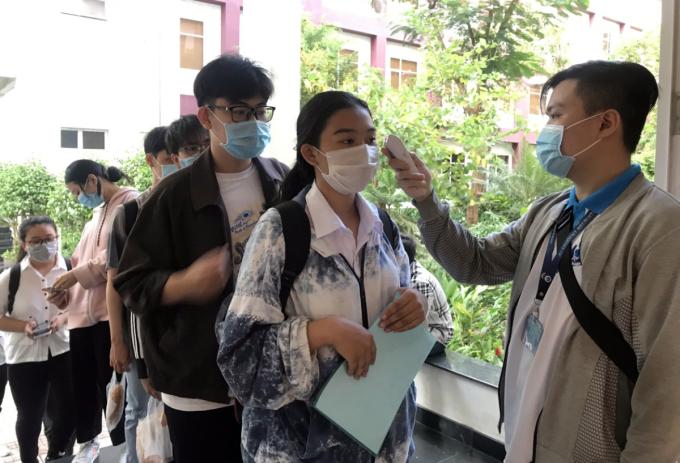 Thí sinh được đo thân nhiệt trước khi vào điểm thi trường Đại học Quốc tế (Đại học Quốc gia TP HCM) tại TP Thủ Đức. Ảnh: Mạnh Tùng.