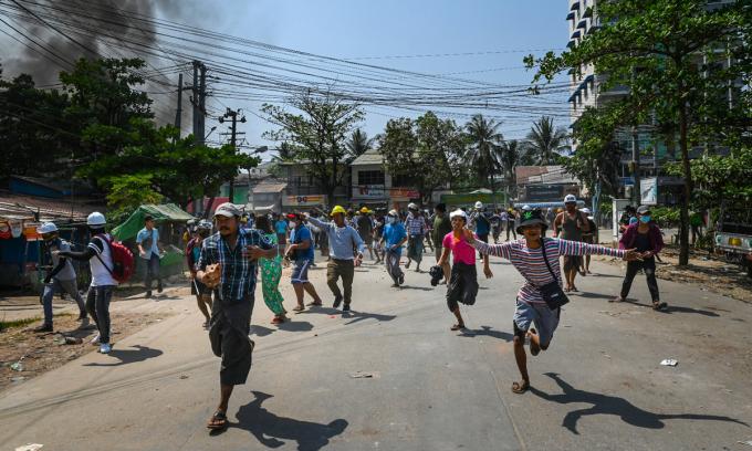 Người biểu tình bỏ chạy tán loạn trong cuộc trấn áp của lực lượng an ninh tại Yangon hôm 19/3. Ảnh: AFP.
