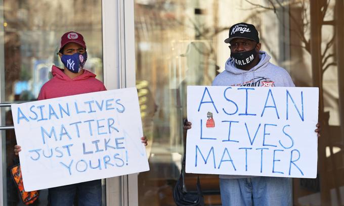 Hai người cầm bảng phản đối làn sóng thù ghét người gốc Á ở Manhattan, thành phố New York hôm 30/3. Ảnh: AFP.