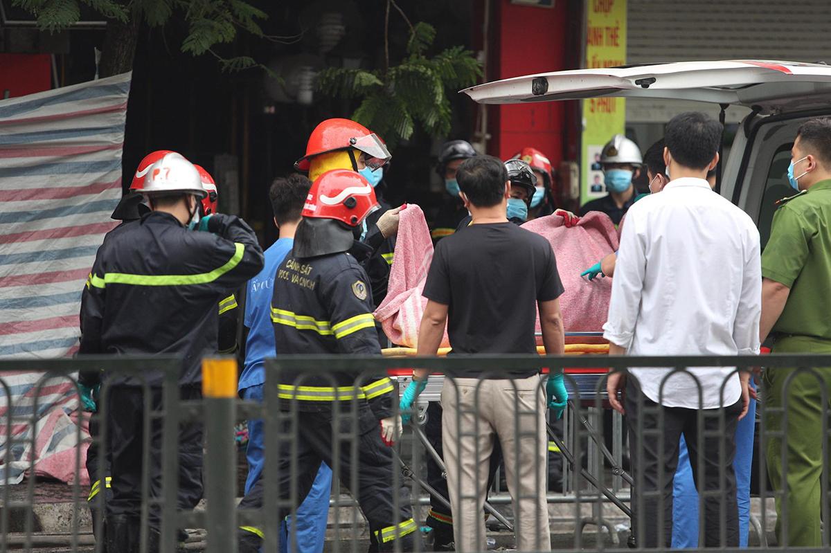 Lực lượng cứu hộ đưa một thi thể ra khỏi ngôi nhà sáng 4/4. Ảnh: Nguyễn Định