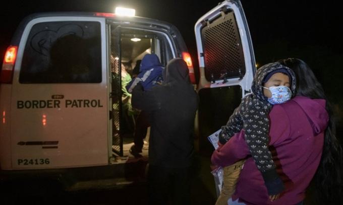 Người di cư từ Trung Mỹ lên chiếc xe của lực lượng tuần tra biên giới Mỹ sau khi vượt sông Rio Grande vào thành phố Roma, bang Texas hôm 28/3. Ảnh: AFP.